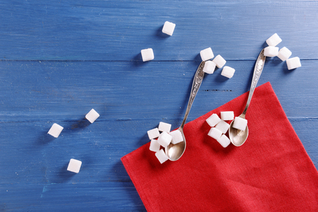 Creative musical notes made of spoon and sugar with red cotton napkin on blue wooden background Banque d'images