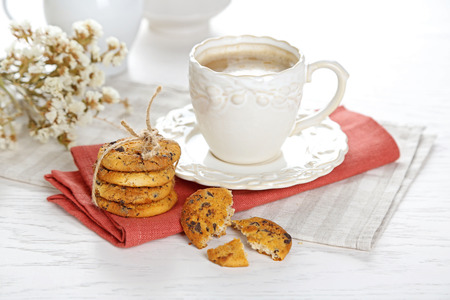 Cup of coffee and pile of tasty cookies with chocolate crumbs on white wooden table Stok Fotoğraf