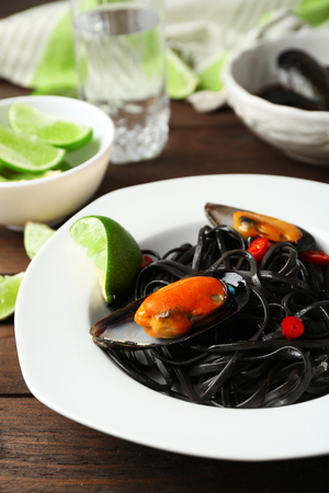 Cooked pasta, mussel and lime on brown wooden background