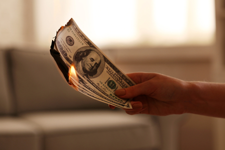 Woman burning dollars in the room
