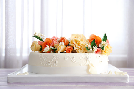Elegant wedding cake decorated with flowers on table in the room