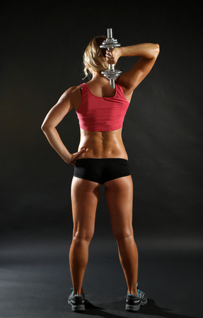 Athletic woman with dumbbells on dark background