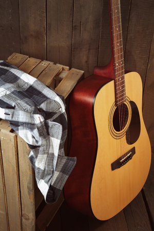 Guitar and shirt left on crate on wooden wall background Stock Photo
