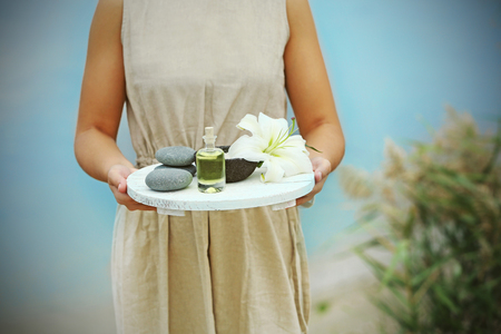 Female hands with tray of spa products, outdoors Imagens