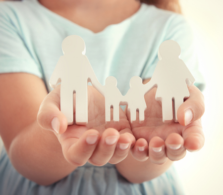 Concept of united family - figures of parents and kids in girls hands Foto de archivo