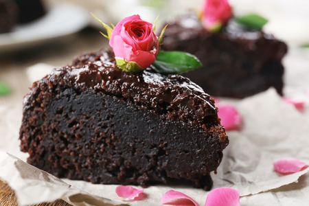 Piece of chocolate cake decorated with flowers on brown wooden table, close-up Stock Photo