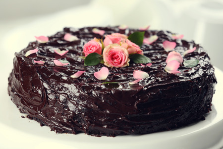 Chocolate cake decorated with flowers on the table, close-up