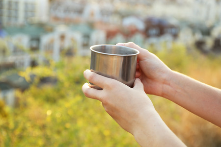Metal touristic tea cup in female hands Standard-Bild