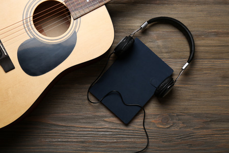 Acoustic guitar, headphones, notebook and microphone on wooden background, close up
