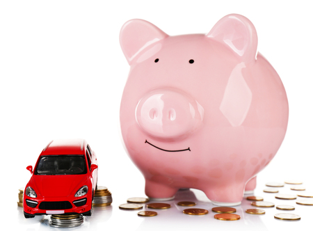 Piggy bank with car toy and coins around, isolated on white Banque d'images - 102900686