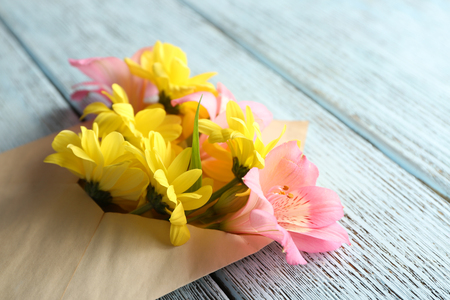 Pink alstroemeria and yellow chrysanthemum in envelope on wooden background Stock Photo