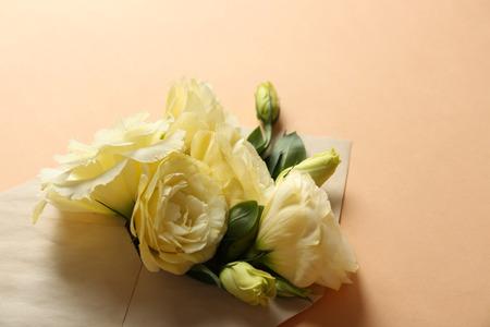 White eustoma in envelope on beige background Reklamní fotografie