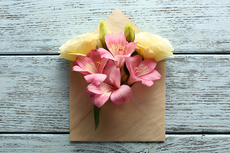 White eustoma and pink alstroemeria in envelope on wooden background Stock Photo