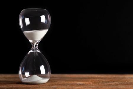 Hourglass on wooden table on black background 版權商用圖片