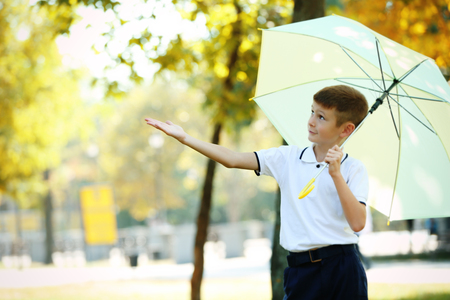 Boy under big creamy umbrella at the park