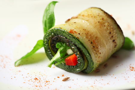 Zucchini roll with cheese, bell peppers and arugula on plate, close-up Imagens