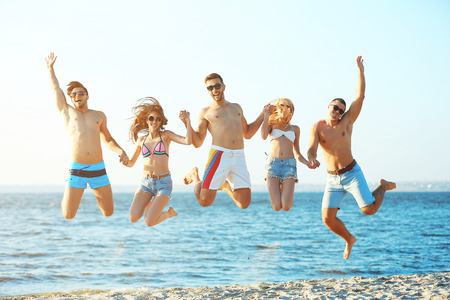 Happy friends jumping at the beach, outdoors Stock Photo