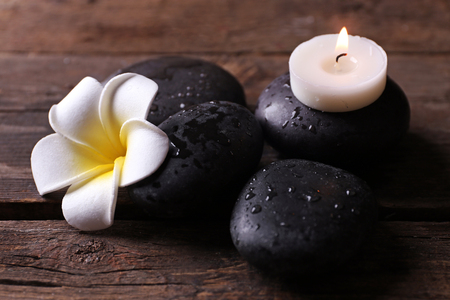 Relaxing concept - fragipani flower, pebbles and candles on wooden background