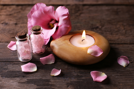 Tenderness composition of alight candle with flower petals on wooden background Stock Photo