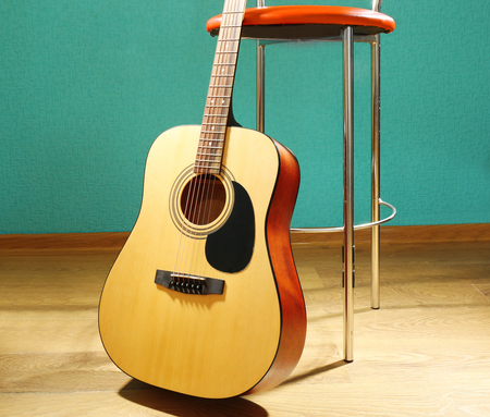 Guitar with bar stool on the floor against blue background in the studio, close up