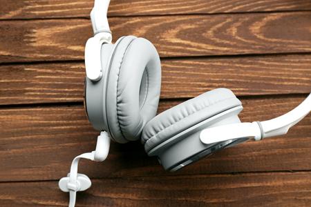 Headphones on brown wooden background Фото со стока