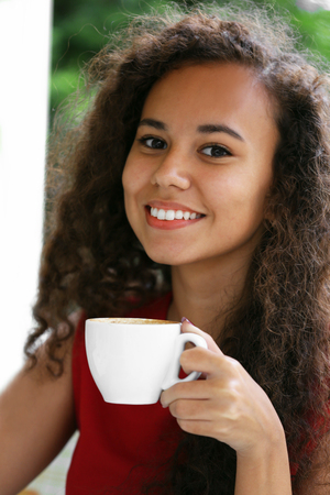 Close up portrait of young pretty woman drinking coffee