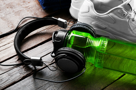 Headphones and sport equipment on old wooden background Stock Photo