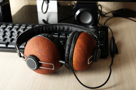 Headphones and keyboard on wooden table