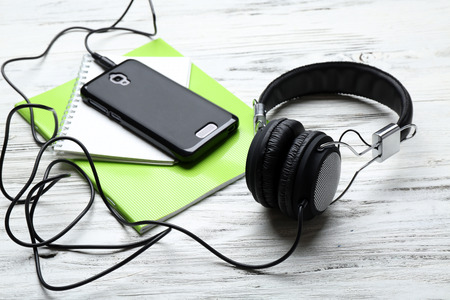 Headphones with notebooks and smartphone on wooden table