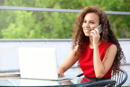 Pretty business woman in red dress with laptop speaks by cellphone at summer terrace