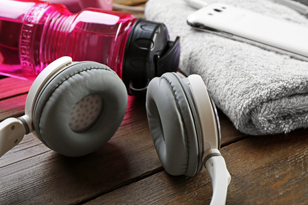 Headphones and sport equipment on old wooden background Фото со стока