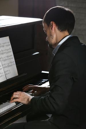 Musician plays piano in dark studio