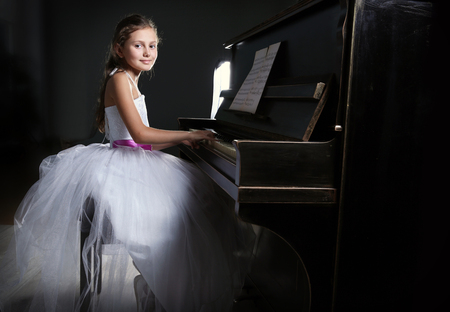 Cute little princess girl plays piano in the dark room
