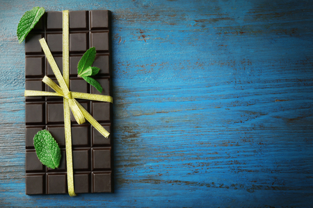 Dark chocolate bar with colorful bow on color wooden background Stockfoto