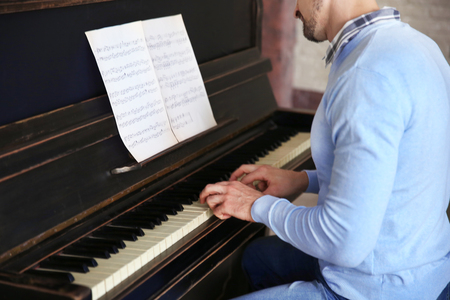 Handsome man plays piano in the class Standard-Bild