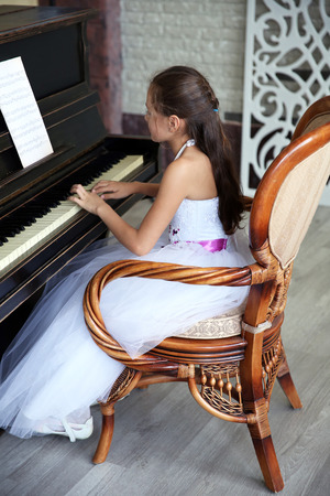 Cute little princess girl plays piano sitting in vintage chair in the studio Standard-Bild
