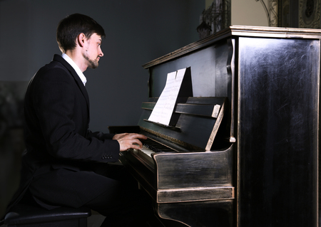 Handsome man in black suit plays piano in the dark studio Фото со стока