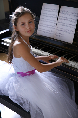 Cute little princess girl plays piano in the studio Stock Photo