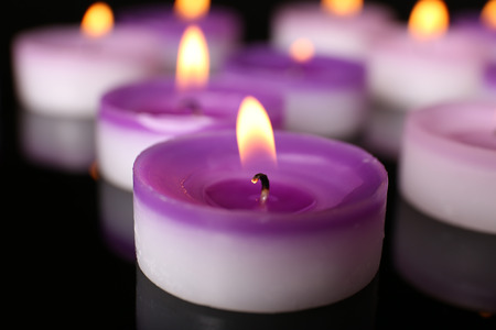 Many burning small candles on dark background, close-up Stock Photo