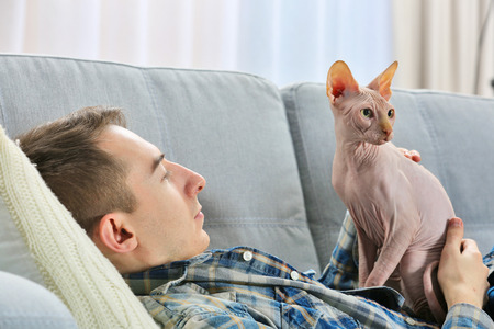 Young man lies with cat on couch at home Stock Photo