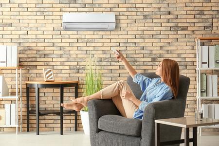 Jonge vrouw die airconditioner aanzet terwijl ze thuis in een fauteuil zit