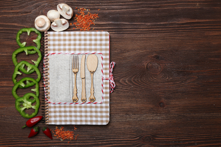 Decorated composition of recipe book and ingredients on wooden background, copy space Standard-Bild