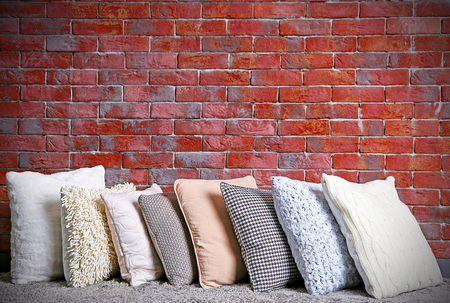 Multicoloured pillows on a brick wall background Archivio Fotografico