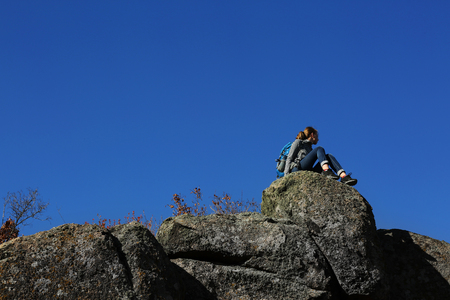 Woman sitting on the top of the mountain