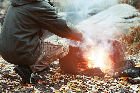 Man making fire in mountains 写真素材