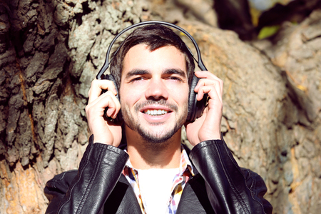 Young man in headphones on tree background