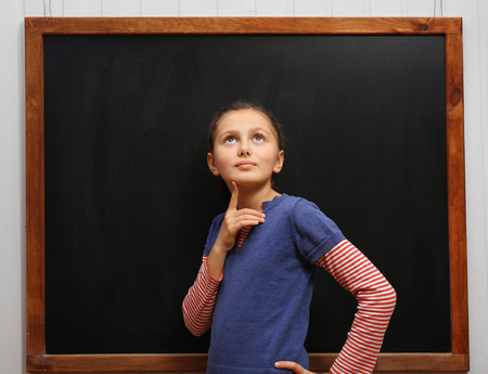 Cute girl posing at the clean blackboard, in the classroom Imagens