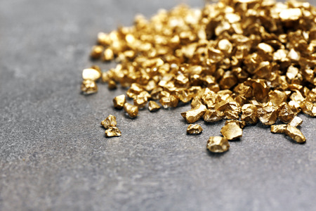 A pile of Gold nugget grains, on cement background Stock Photo
