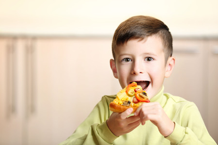 Little boy eating pizza at home