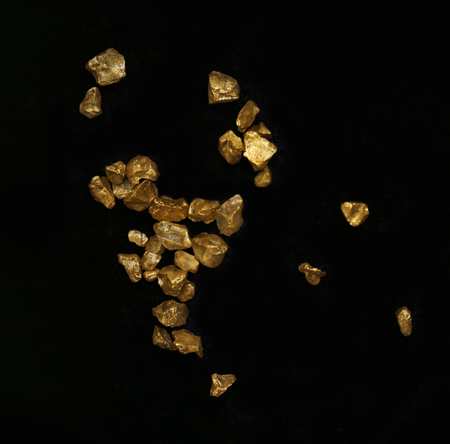 Scattered gold nugget grains, on black background